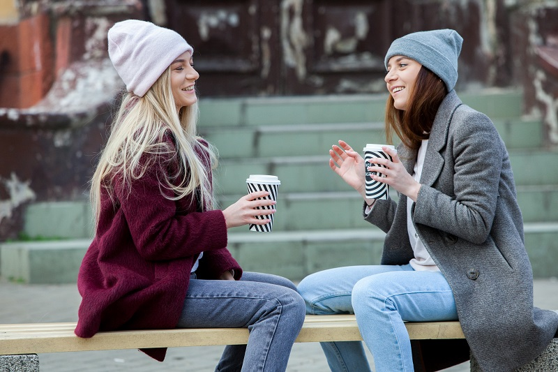 two girls having a coffee and cahtting on a street bench in Winter